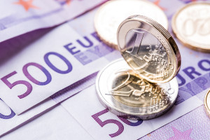 Several 500 euro banknotes and coins are adjacent. Symbolic photo for wealt.Euro coin balancing on stack with background of banknotes.