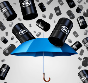 Falling oil protection concept as a group of crude petroleum barrels raining down with a blue umbrella as a security metaphor as a symbol for declining prices in fossil energy due to oversupply.