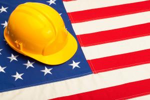 Construction helmet laying over USA flag - studio shoot